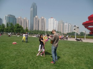 Qingdao man takes a break from blowing bubbles with his son to teach us how to fly a kite.